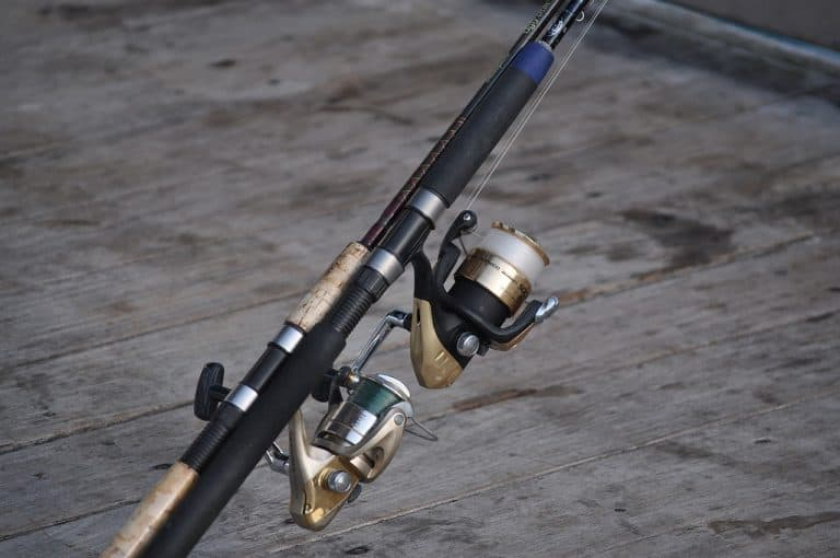 Two spinning fishing reels on pier
